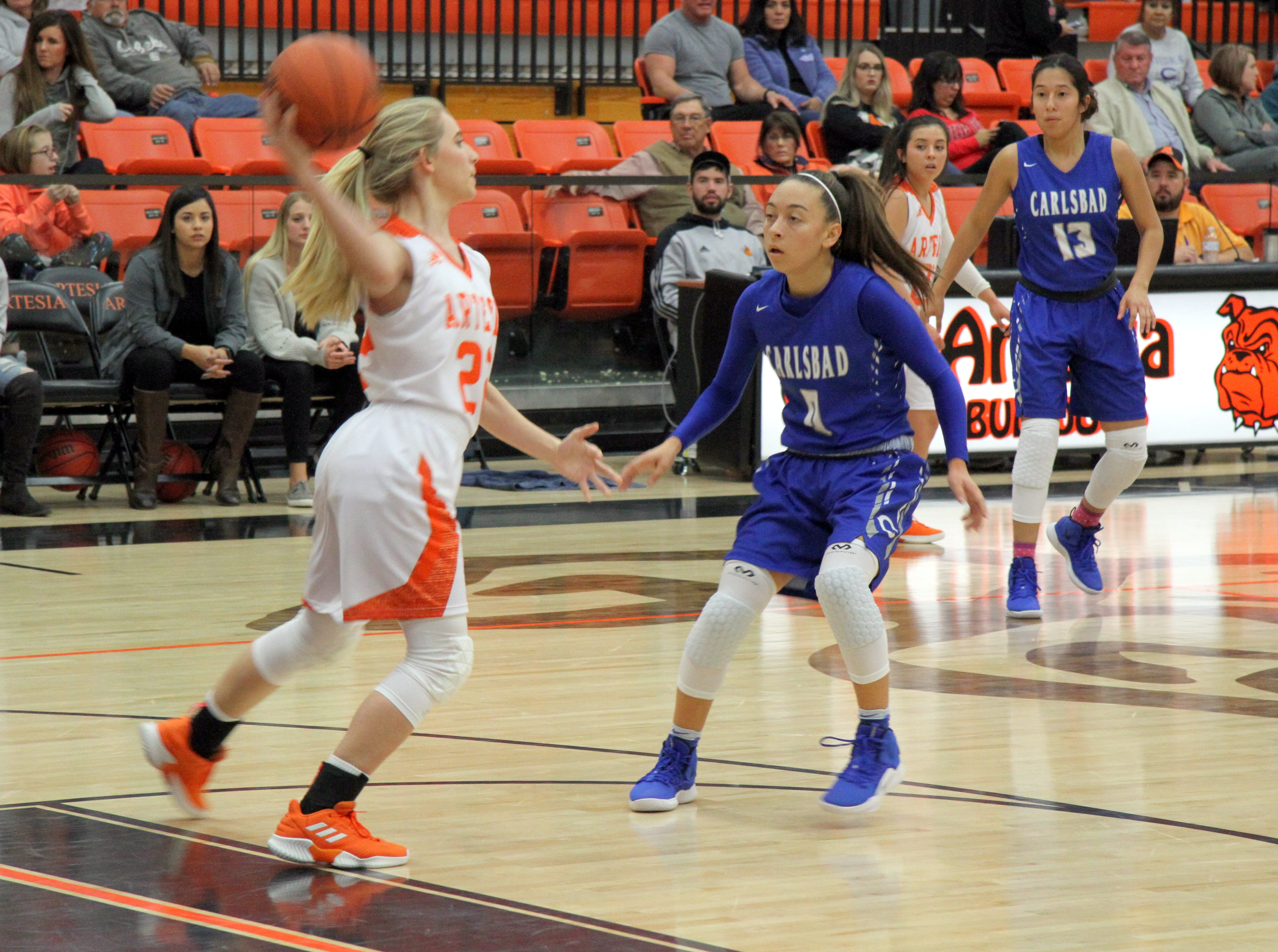Artesia's Faith Evans (22) looks for an open teammate while Carlsbad's Bailee Molina guards her during Saturday's third-place game in Artesia.