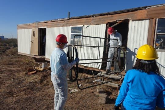 Volunteers removed debris from a dilapidated structure before it was torn down to make way for a new home.