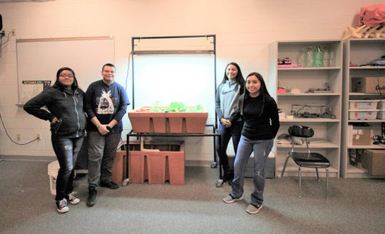 Mesaclero Apache school STEM students stand in front of  their Aqua Phonics project. Lani Cojo, Cedric Barcus, Madisyn and Shylo Klienkole.