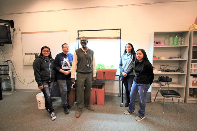 Students and Mr. Raynor from Mescalero Apache school stand in front of their aqua phonics project, that grows vegetables, which is a part of the STEM program.