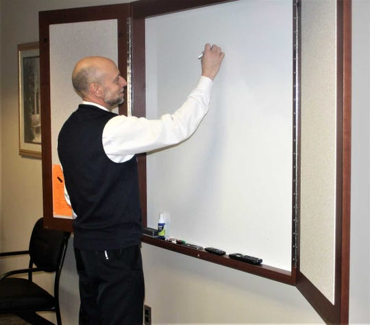 Personalized Nursing Light House clinical director Stephen Wiland uses the Canton facility's white board.