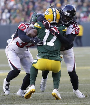 Atlanta Falcons cornerback Brian Poole (34) and cornerback Desmond Trufant (21) tackle Green Bay Packers wide receiver Davante Adams (17) in the fourth quarter Sunday, December 9, 2018, at Lambeau Field in Green Bay, Wis.  Dan Powers/USA TODAY NETWORK-Wisconsin