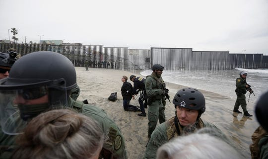 Immigrant rights activists are arrested by border patrol agents during a protest at the border wall in San Diego on Monday, Dec. 10, 2018.