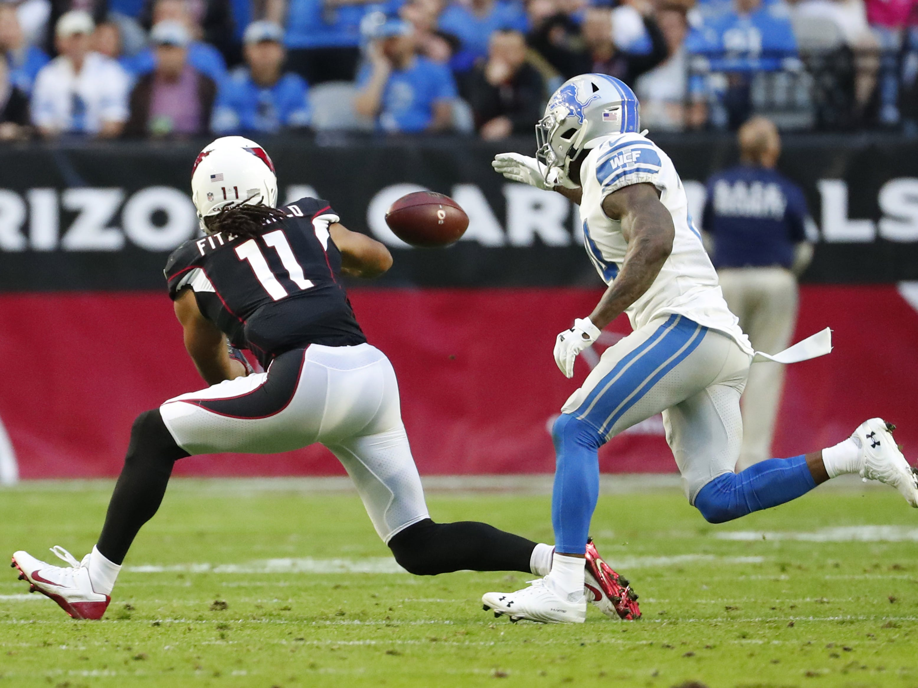 Arizona Cardinals wide receiver Larry Fitzgerald (11) catches a pass while defended by Detroit Lions cornerback Nevin Lawson (24) during the second half in Glendale, Ariz. December 9. Fitzgerald broke Jerry RiceÕs record for most career receptions with one team.