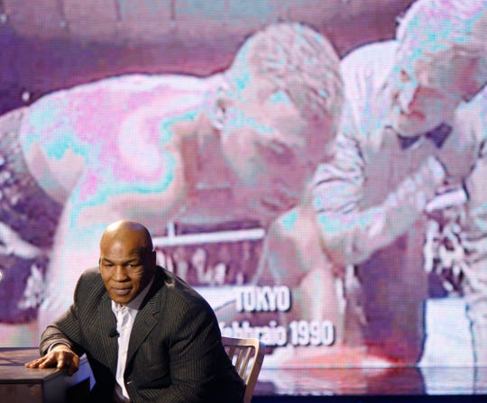 Former heavyweight champion Mike Tyson watches a video of himself getting knocked out by Buster Douglas, during an appearance on an Italian television show on Jan. 25, 2010.