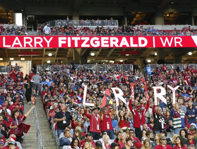 Arizona Cardinals fans hold signs for wide receiver Larry Fitzgerald during the second half against the Detroit Lions in Glendale, Ariz. December 9.
