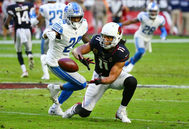 Arizona Cardinals wide receiver Larry Fitzgerald makes his 1,282 career reception against Detroit Lions' Nevin Lawson in the third quarter during a game on Dec. 9 at State Farm Stadium. Fitzgerald set an NFL record for most career receptions with one team, passing Jerry Rice.