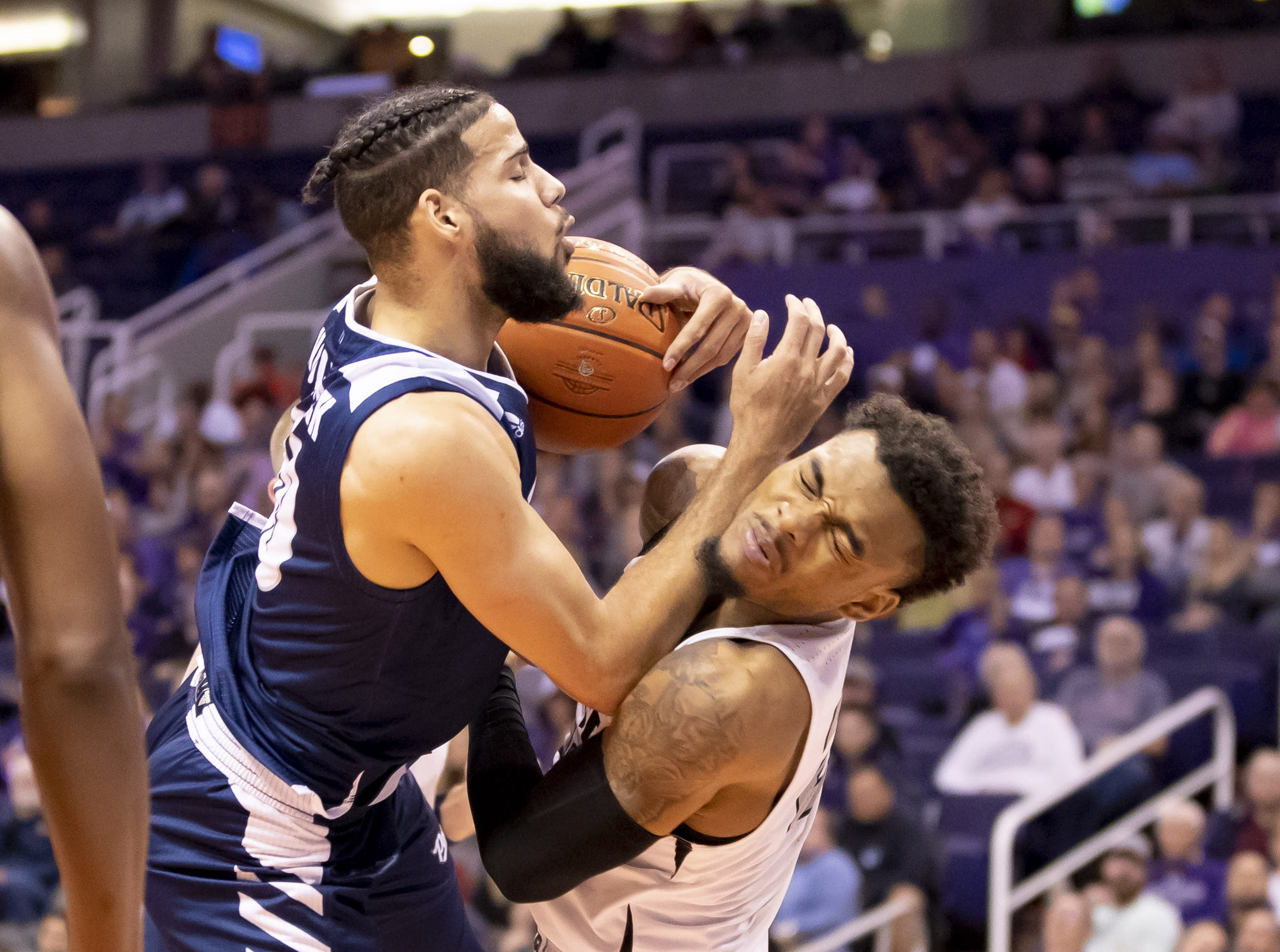 Forward Caleb Martin (10) of Nevada Wolf Pack and guard Carlos Johnson (23) of the Grand Canyon Antelopes collide during the 2018 Jerry Colangelo Classic at Talking Stick Resort Arena on Sunday, December 9, 2018 in Phoenix, Arizona.