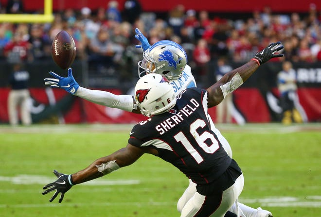 Detroit Lions corner back Darius Slay intercepts a pass and returns it for a touchdown agianst Arizona Cardinals wide receiver Trent Sherfield in the third quarter during a game on Dec. 9 at State Farm Stadium.