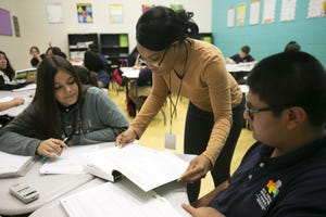 Math teacher Kori Hayles helps Angelina Parr, 12, and  Raul Samano, 12, in the seventh grade math class at the NFL YET College Prep Academy, a 7th-12th grade charter school in South Phoenix, on Nov. 5, 2018.