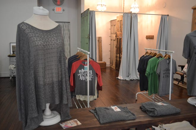T-shirts, ladies wear, and kids clothing are displayed in front of the dressing rooms, whose walls are built of vintage doors.
