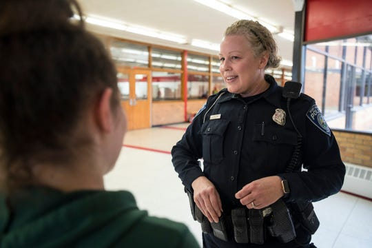 Port Huron Police Officer Laura Phillips talks with a student waiting for a bus after school is released Monday, Dec. 10, 2018 at Port Huron High School.