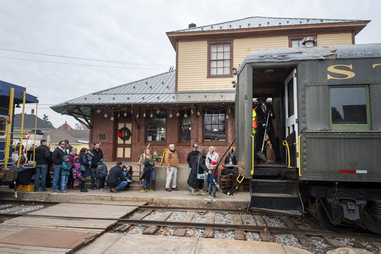 Vincent Skinner, assistant stationmaster, sweeps out the entrance to a coach before riders board the Santa Ride on the Stewartstown Railroad.
