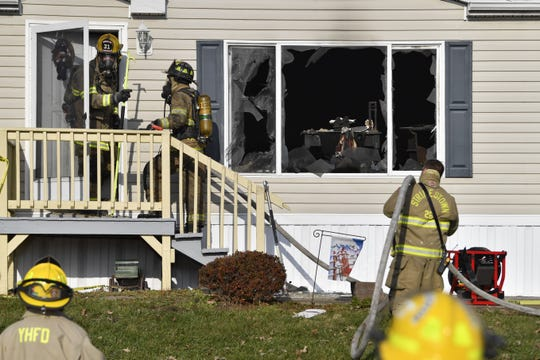 Firefighters work on the scene of a mobile home fire that police say was purposely set in Newberry Township on Monday.