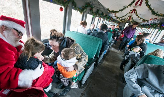 Chip Welsh, playing Santa, at the Stewartstown Railroad on Sunday December 9, 2018 holds Brea Graham, age 3, while her mother Kristin talks to her during a Santa Ride.