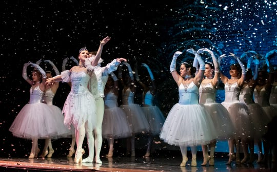 Local performers join the Reno Dance Company's Snow Queen and King as snow falls.