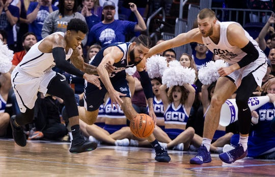 Grand Canyon's Damari Milstead (11) and Michael Finke (43) double-team Nevada's Cody Martin during the second half Sunday in Phoenix.