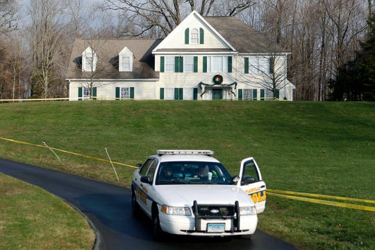 In this Dec. 18, 2012, file photo, a police cruiser sits in the driveway of the home of Nancy Lanza in Newtown, Conn., the Colonial-style house where she had lived with her son Adam Lanza. Documents from the investigation into the massacre at Sandy Hook Elementary School are shedding light on the Lanza's anger, scorn for other people, and deep social isolation in the years leading up to the shooting. He fatally shot his mother there before driving to the school and ultimately killed himself. (AP Photo/Jason DeCrow, File)