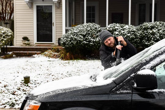 Danny Pace scrapes snow and ice off a car in Salisbury on Monday, Dec 10, 2018.