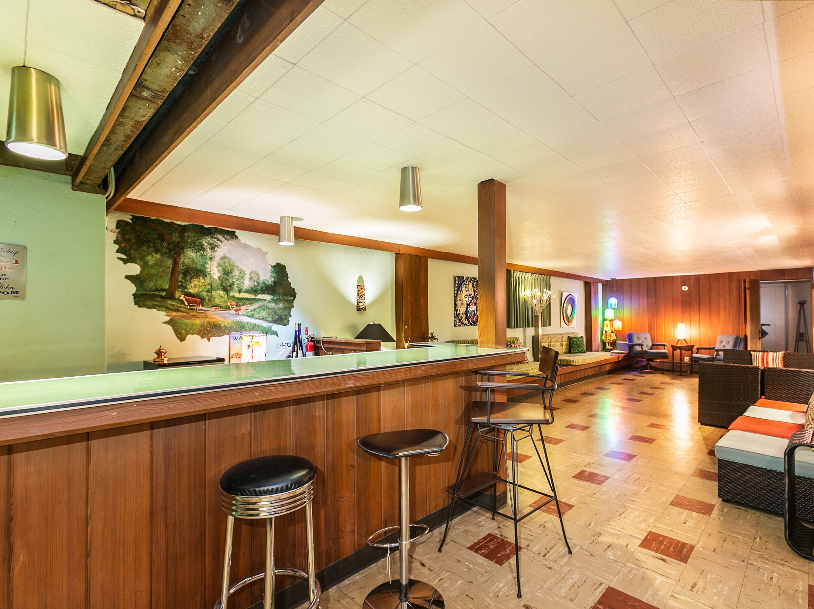 The downstairs bar also is frozen in time, with boomerang Formica on the counter and original tile and built-ins. The mural on the wall was completed in 1960 by C. Summey. Kyaw says they wouldn't dream of doing away with it. As an artist himself, he has far too much respect for it.