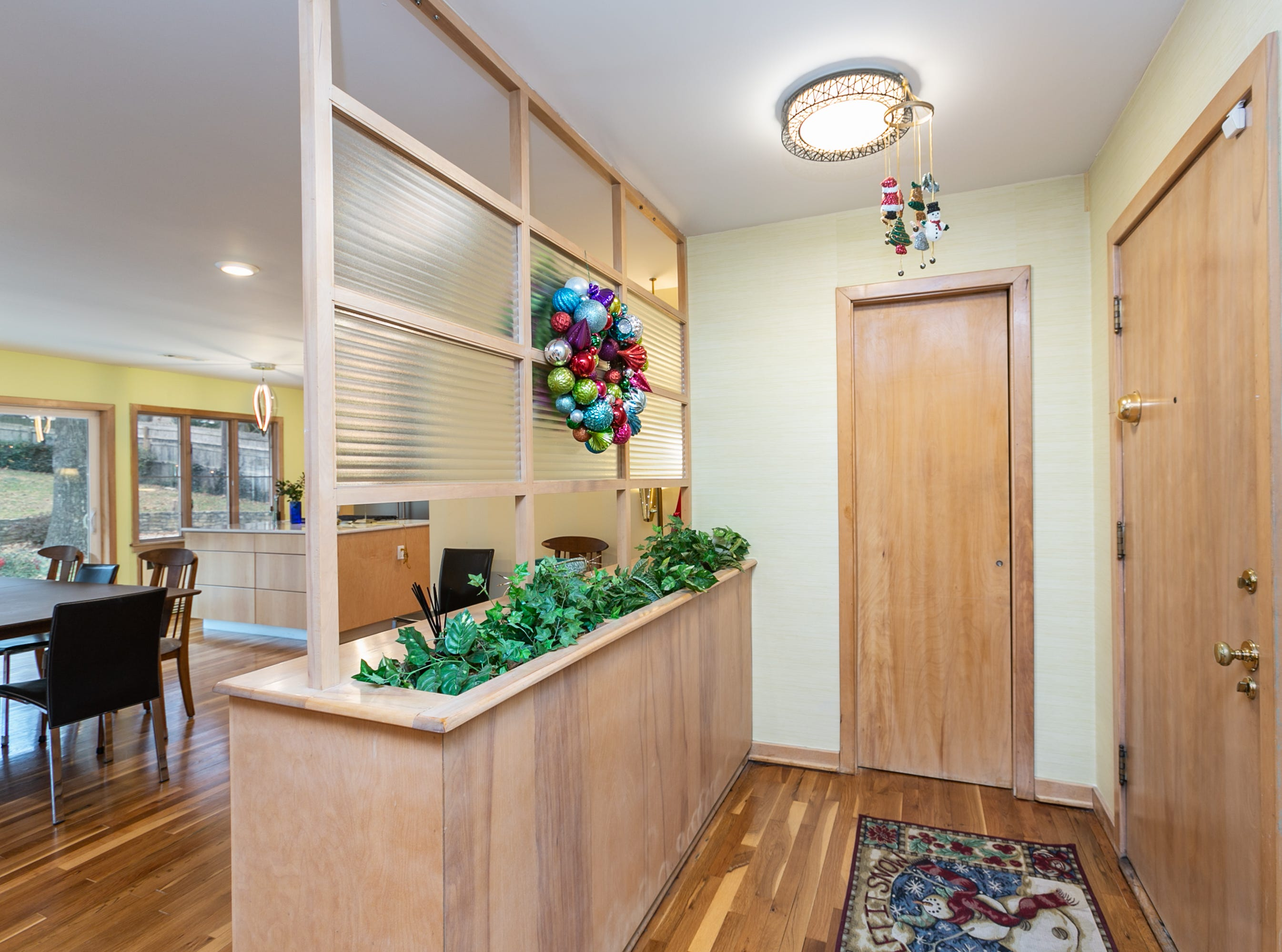 The couple kept as many original features as possible, including this entry divider, the hardwood floors and even the wallpaper.