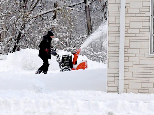 A snow thrower is used to clear snow from a parking lot around Warehouse Auto Repair on Richmond Road in Staunton on Monday, Dec. 10, 2018.