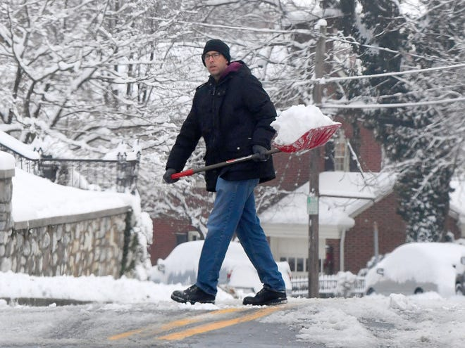 One individual clears snow from around a parked car one scoop at a time on East Beverley Street following a snowstorm in Staunton on Monday, Dec. 10, 2018.