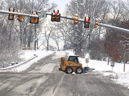 A skid steer cruises along Frontier Drive and through the intersection at Barterbrook Road following a snowstorm in Staunton on Monday, Dec. 10, 2018.