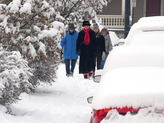 Ladies walk together along a snow-covered sidewalk adjacent West Frederick Street following a snowstorm in Staunton on Monday, Dec. 10, 2018.