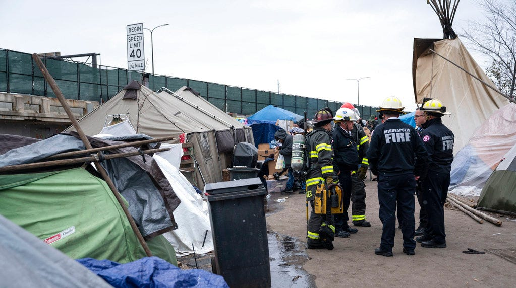 Authorities stand at a homeless encampment where multiple tents caught fire Nov.19 in Minneapolis. People in the camp are expected to move to large, heated tents starting Tuesday, Dec. 11.