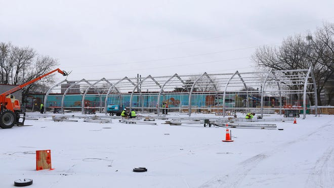 Construction workers erect the metal frame Nov. 28 for housing at the site of the new navigation center that will replace the Hiawatha homeless encampment in Minneapolis.