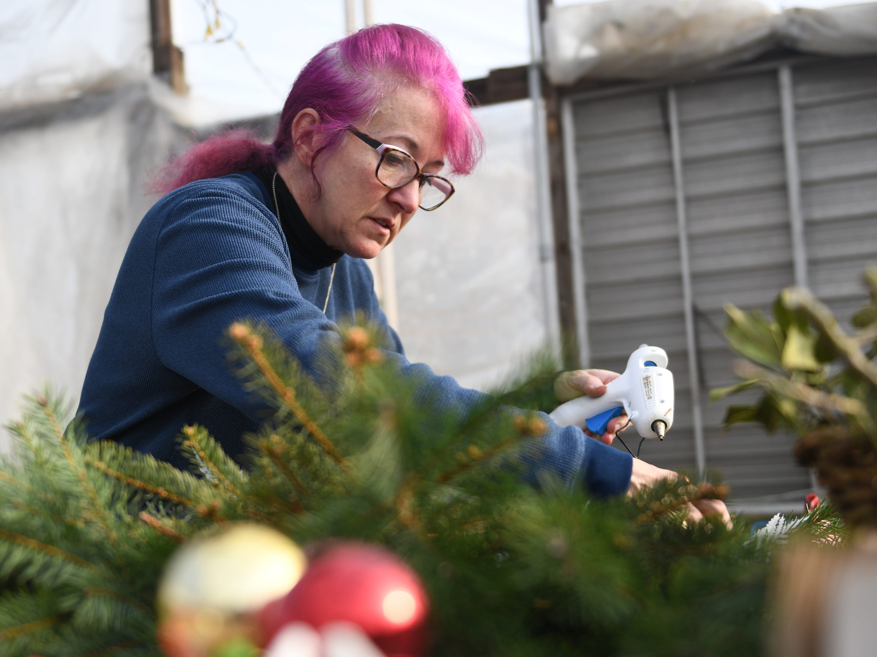 Selina Rose of Newfield decorates a Christmas wreath while working at Huffman Farms in Vineland on Monday, December 10, 2018.