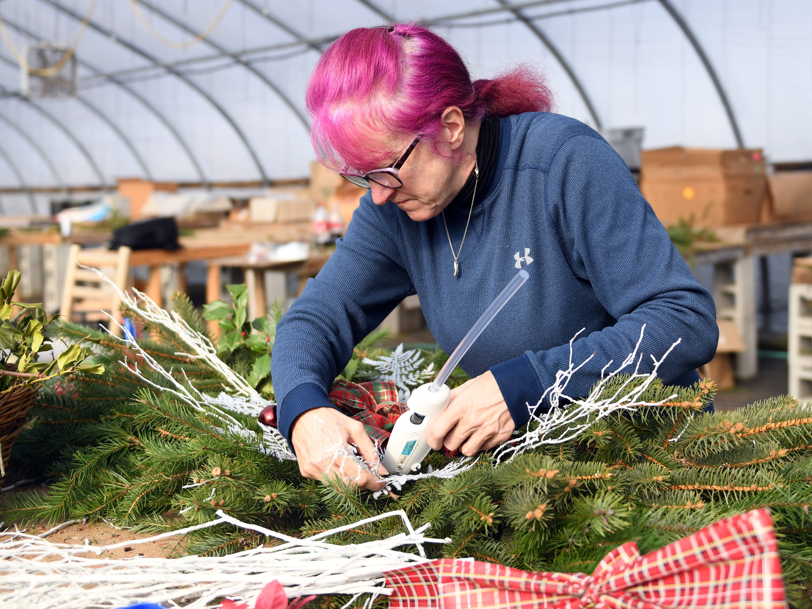 Selina Rose of Newfield decorates a Christmas wreath while working at Huffman Farms on 296 S. Blue Bell Road in Vineland on Monday, December 10, 2018.