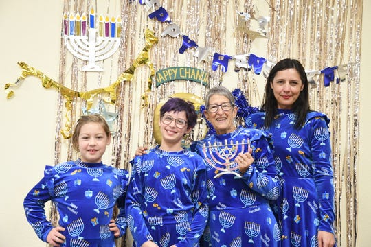 Laurie Hart holds a menorah and poses with her family in matching, Hanukkah-themed dresses at Congregation B'Nai David in Visalia.