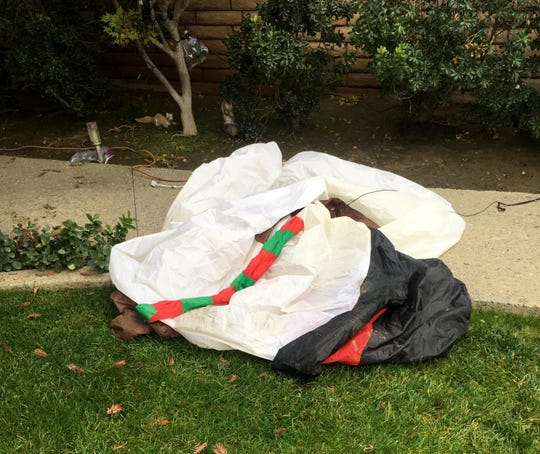 A 12-foot snowman inflatable is slashed in front of Linda Fry's east Visalia home.