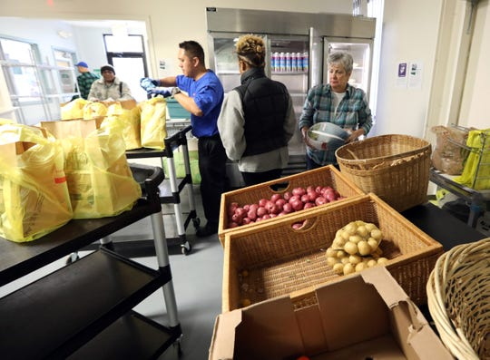 Volunteers Marie Hodge, far right, and Jeff Santos, third from right, help people pick up free food at People to People in West Nyack Dec. 6, 2018.