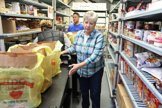 Volunteers Marie Hodge and Jeff Santos help people pick up free food at People to People in West Nyack Dec. 6, 2018.