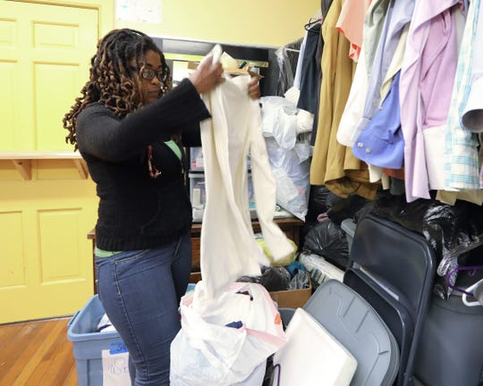 Volunteer Whitney Jaccquet folds donated clothes in the clothing closet at Helping Hands in Spring Valley Dec. 5, 2018.