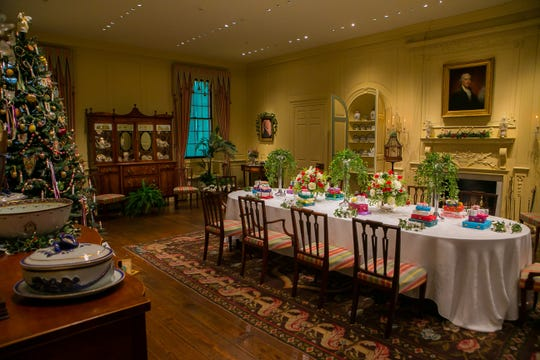 This years dining room display at Winterthur includes colorful presents stacked at each place.