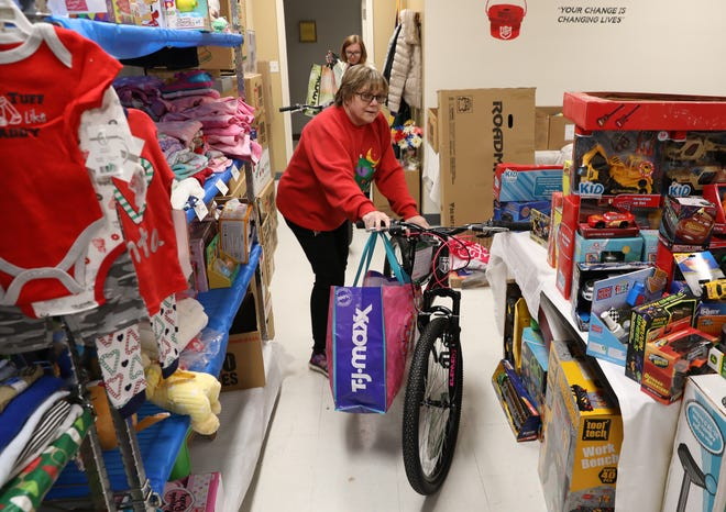 Karen Walker wheels a bike donated for the Angel Tree gift program into the room at the Salvation Army where the gifts were being processed.