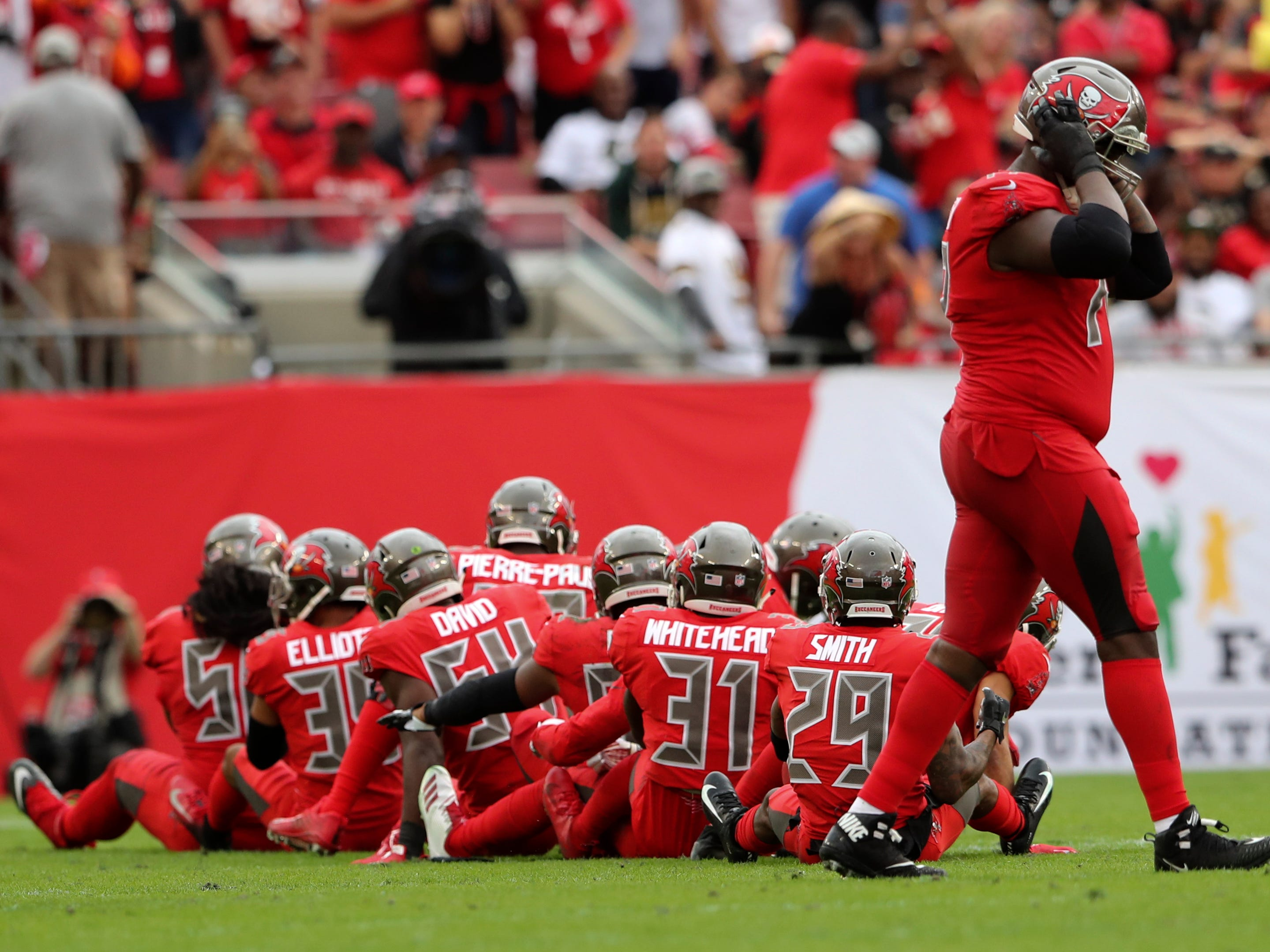 The Tampa Bay Buccaneers defense celebrates an interception during the first half against the New Orleans Saints at Raymond James Stadium.