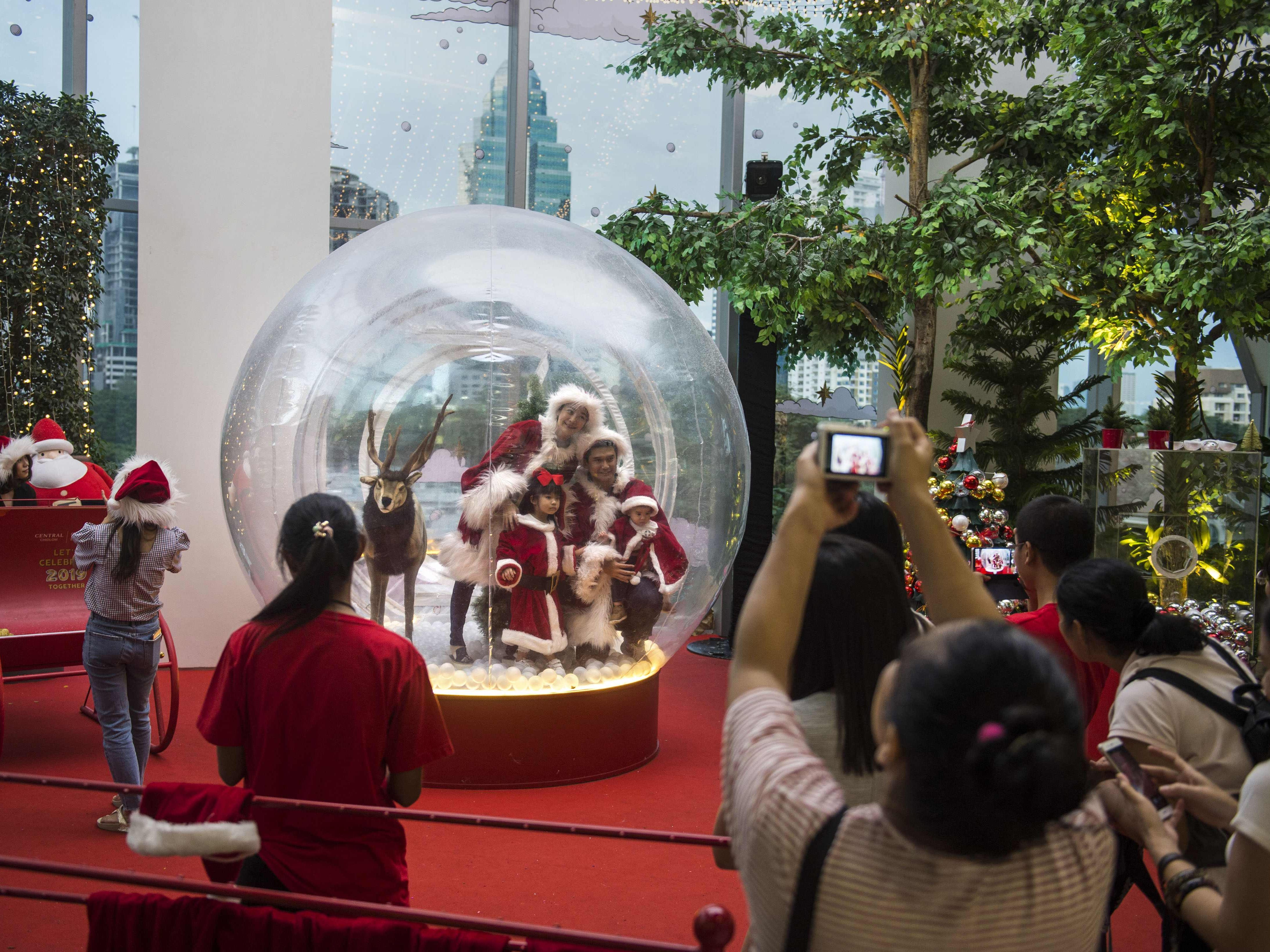 A family wearing Santa costumes poses inside a Christmas decoration at a mall in Bangkok Dec. 9, 2018.