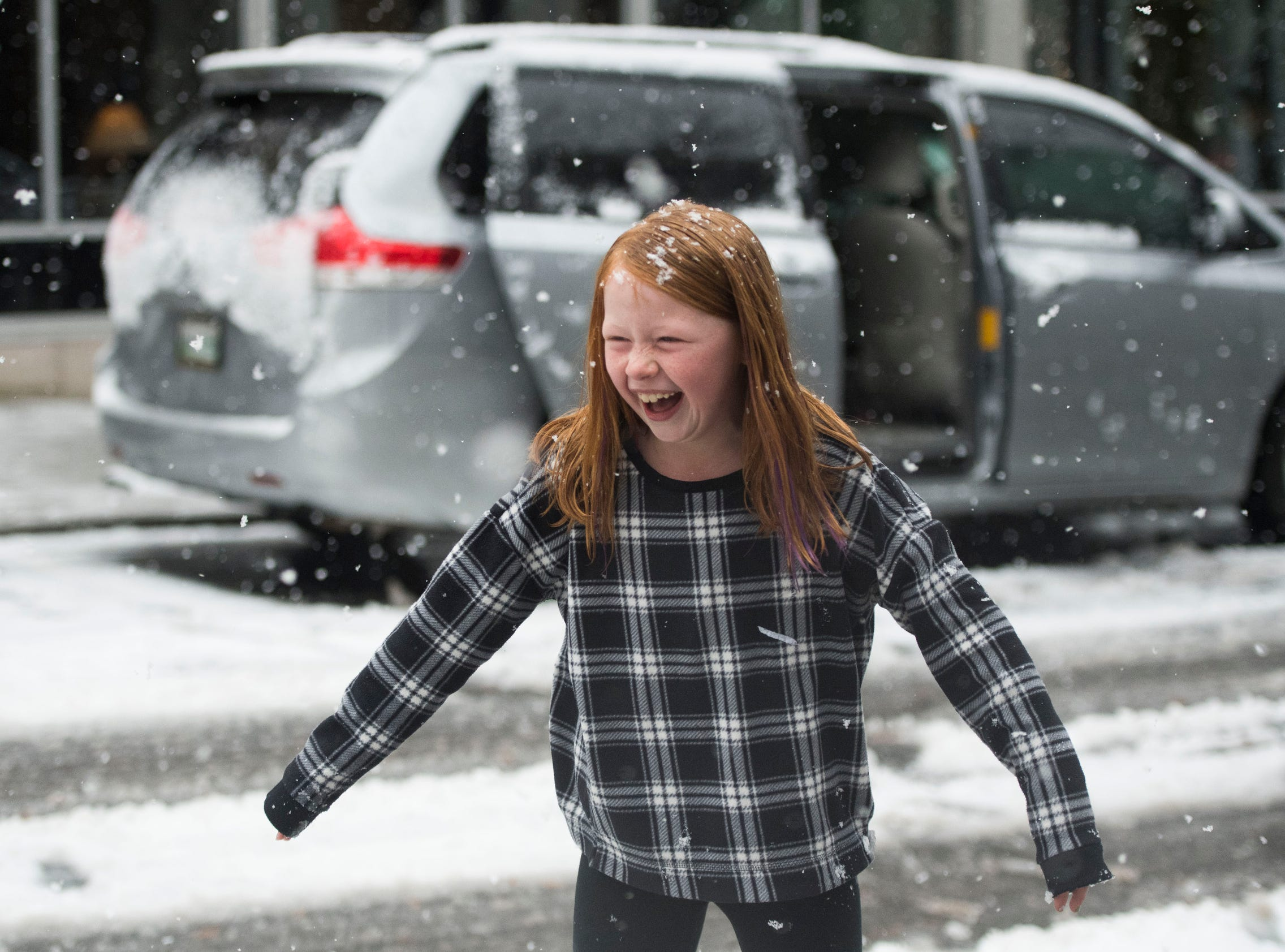 Emilia Eveland, 8, laughs during a snow fight between her brothers and dad in Downtown Knoxville on Sunday,