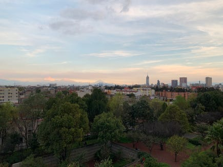 Mountains loom in the background behind the Mexico City skyline as seen from the city's Biblioteca Vasconcelos library.