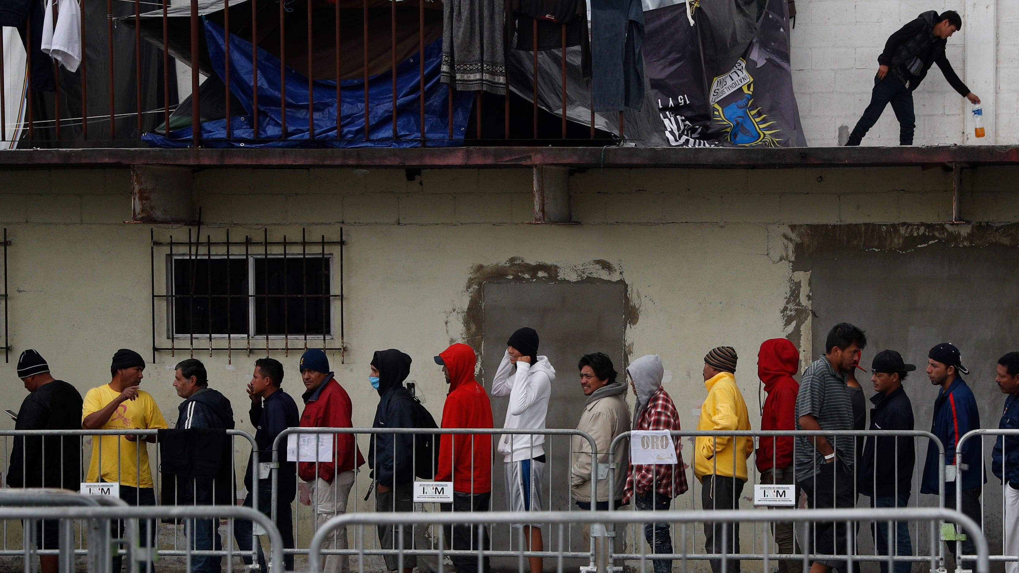 Migrants wait in line to receive free breakfast inside the Barretal migrant shelter, a former concert venue, in Tijuana, Mexico, on Dec. 6, 2018.