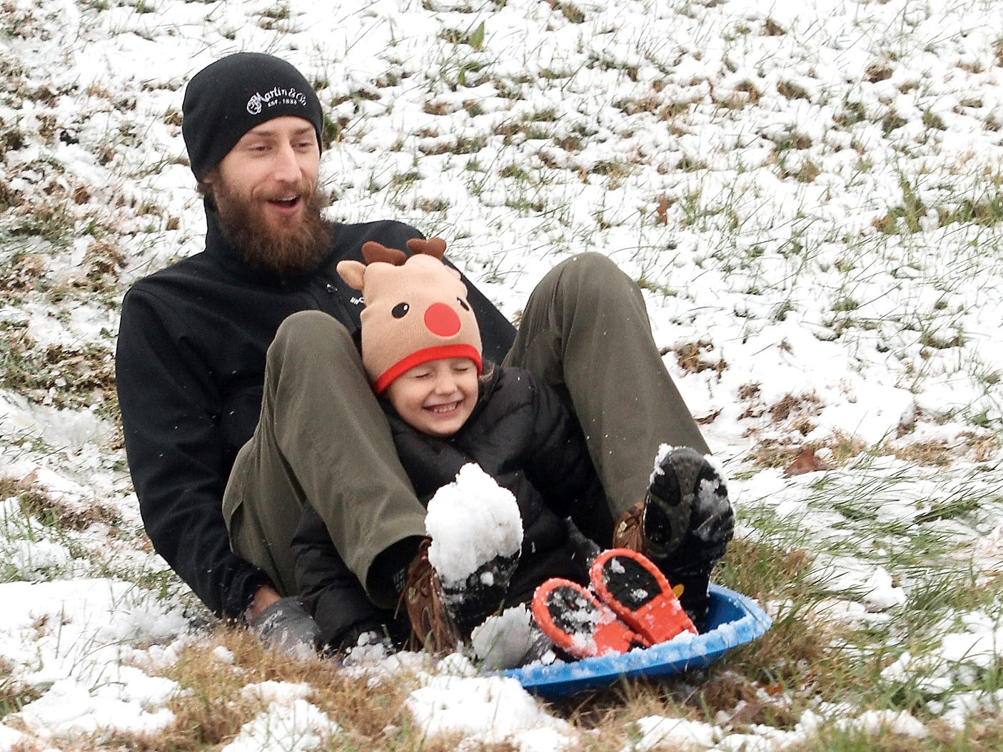 Luke Dunnewold and son Judah enjoy a sled ride down the hill at Foothills Mall in Maryville, Tenn. on Dec. 9. after the first snow of the season.