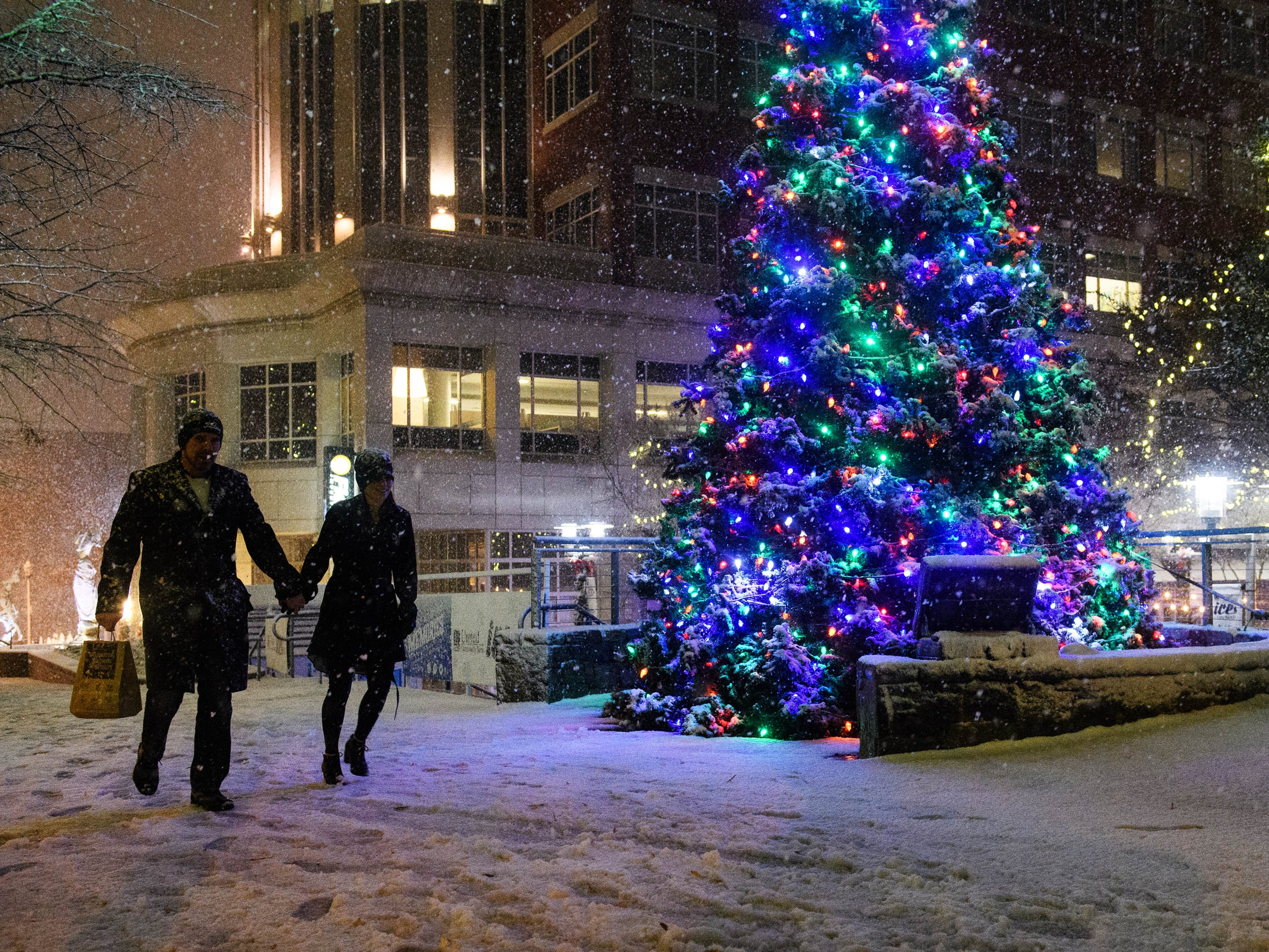 Chad and Shannan Ackerman walk down Main Street as snow begins to fall in Greenville, S.C., on Dec. 9.