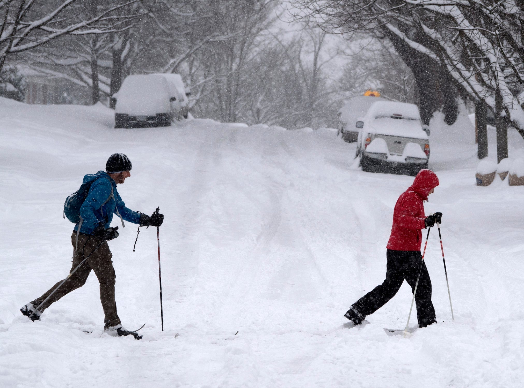 Greg Jans, left, and Stacey Hash get in some cross county skiing in their southwest city neighborhood in Roanoke, Va., Sunday. Snow continues to fall in southwest Virginia.