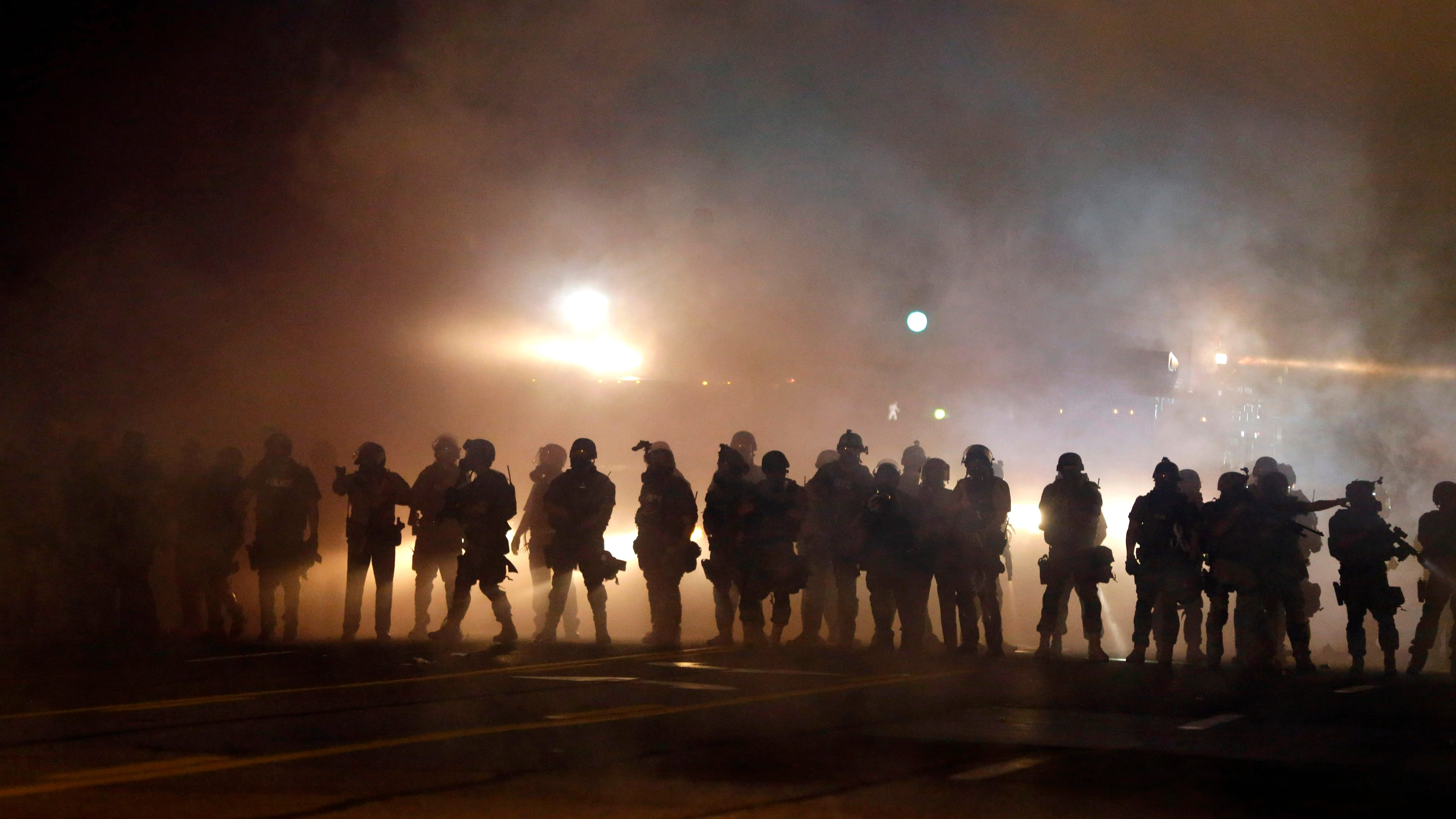 Police walk through a cloud of smoke and tear gas as they clash with protesters during 2014 demonstrations in Ferguson, Missouri. The treatment of protesters in Ferguson prompted many to call for an end to the use of military equipment by police departments.