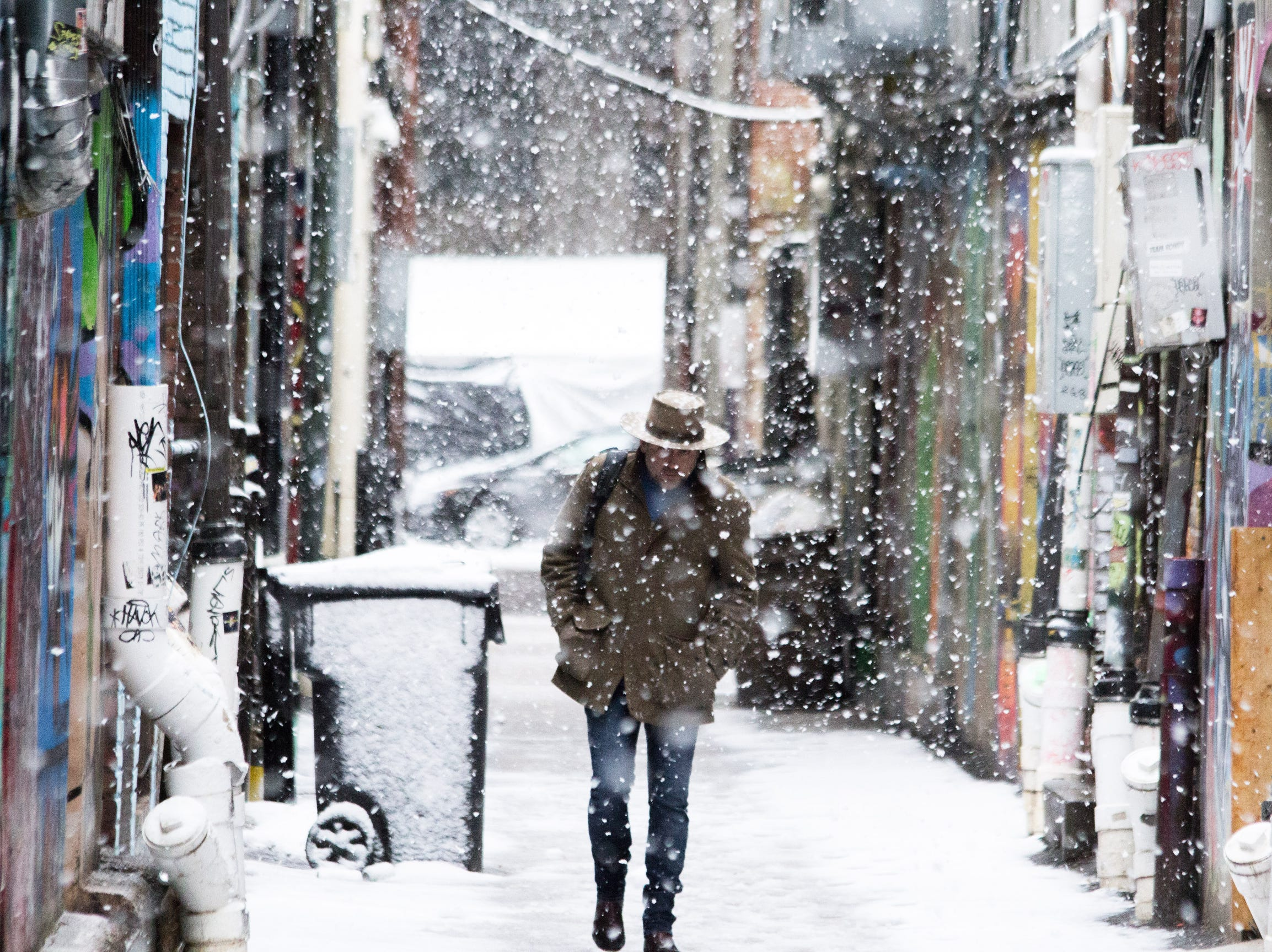 Snow flurries fall in an alley way in Downtown Knoxville in the season's first snow fall, Sunday.